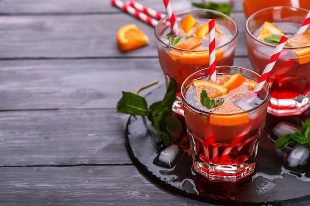 オレンジ、ソーダ、ラズベリーシロップ、ミントの葉と暗い木製のテーブルの上のクールなスカッシュ Premium写真