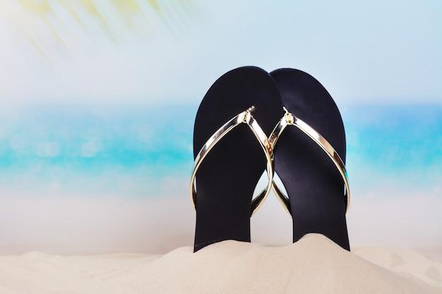 Пляжные шлепанцы на прекрасном песчаном пляже у океана. копировать пространство Premium Фотографии