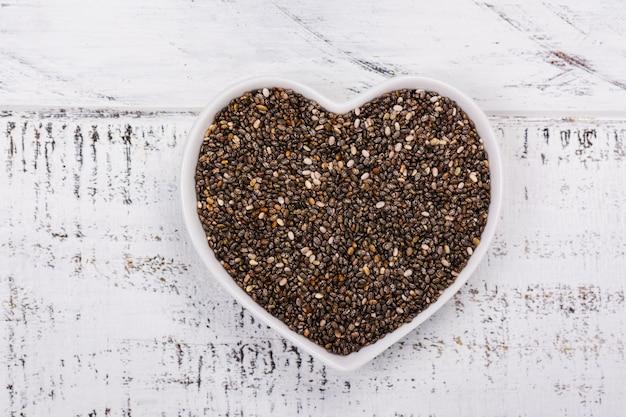 Здоровые семена чиа в миске в форме сердца Premium Фотографии