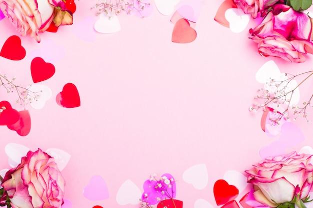 美しいピンクのバラ、装飾的な紙吹雪心とピンクのバレンタインデーの背景にピンクのリボン Premium写真