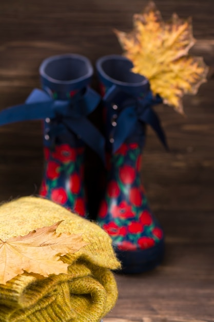 秋の概念:子供の暖かい服装と茶色の木製の背景にゴム長靴。 Premium写真