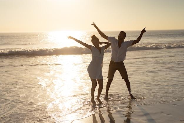 ビーチで一緒に踊るカップル 無料写真