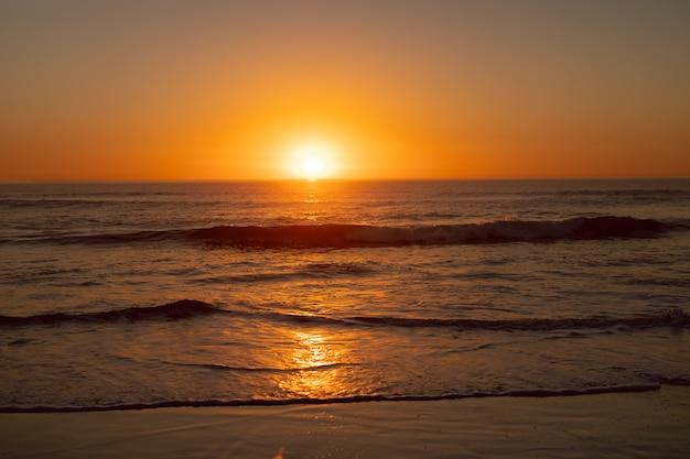 ビーチで海に沈む夕日 無料写真