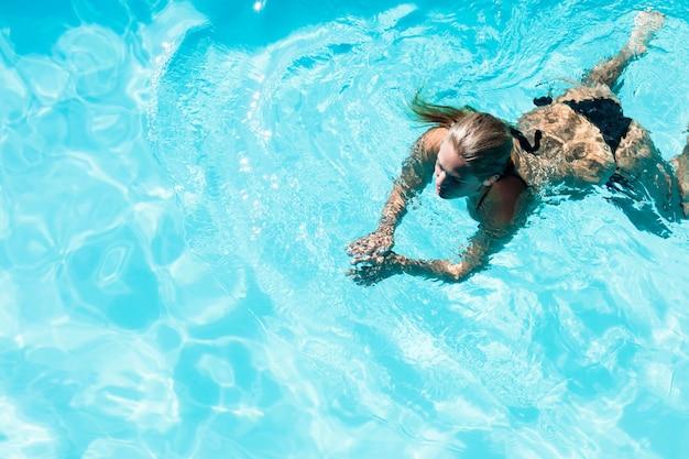 晴れた日にプールで泳いでいる女性に合う Premium写真