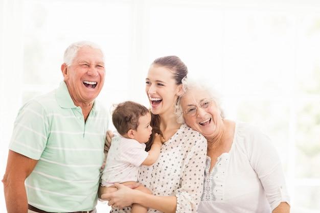 Счастливые бабушка и дедушка играют с внуком дома Premium Фотографии