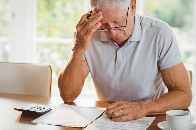 自宅で税務書類を心配している年配の男性 Premium写真