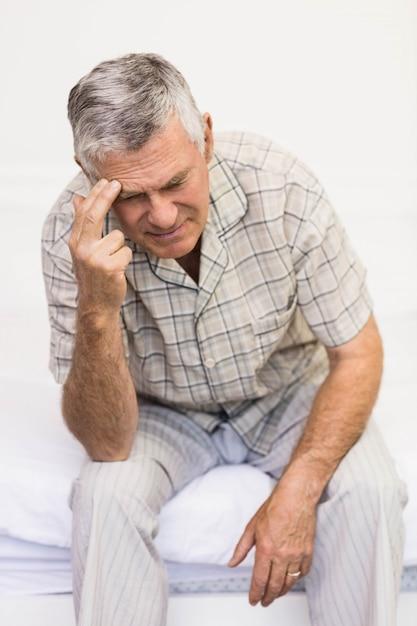 自宅で彼の額に触れる苦しんでいる年配の男性 Premium写真