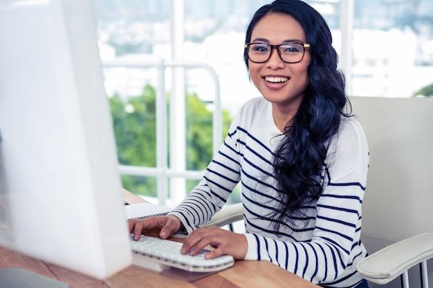 コンピューターを使用して、オフィスでカメラを見て笑顔のアジア女性 Premium写真