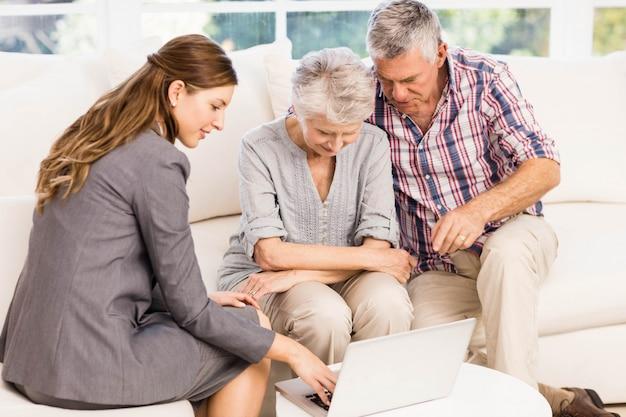 年配のカップルが自宅でラップトップモニターを示す笑顔の実業家 Premium写真