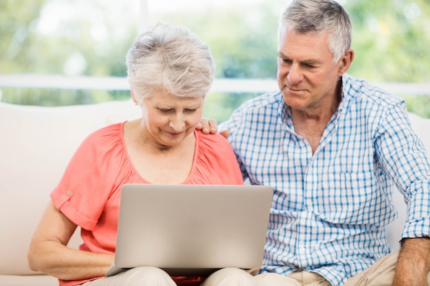 ソファの上のラップトップを使用して笑顔の年配のカップル Premium写真