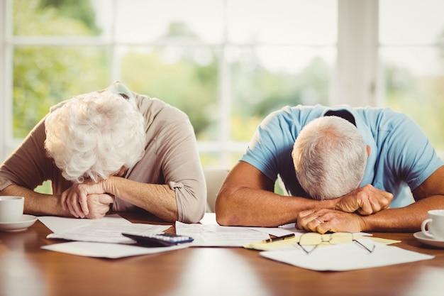自宅で請求書を数えながらタブレットの腕に頭を持つ年配のカップル Premium写真