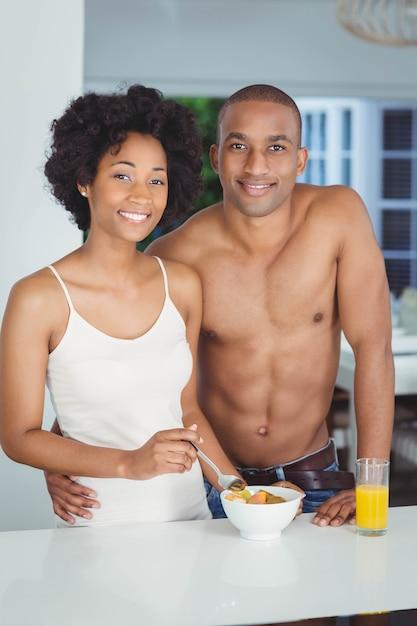 自宅のキッチンで朝食を食べて幸せなカップル Premium写真