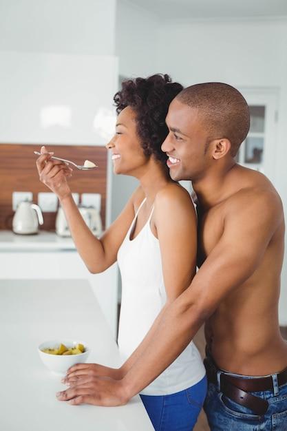 自宅のキッチンで一緒に果物を食べて幸せなカップル Premium写真