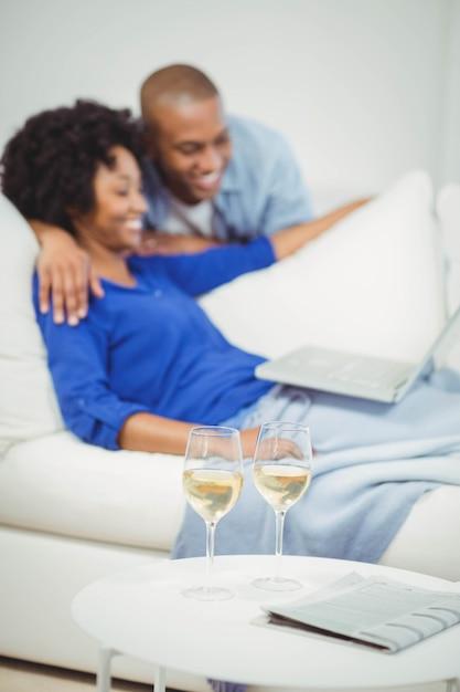 テーブルの上の白ワインのグラスとラップトップを使用してソファの上の幸せなカップル Premium写真