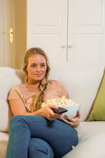 テレビを見て、ソファに座ってポップコーンを食べてきれいな金髪 Premium写真