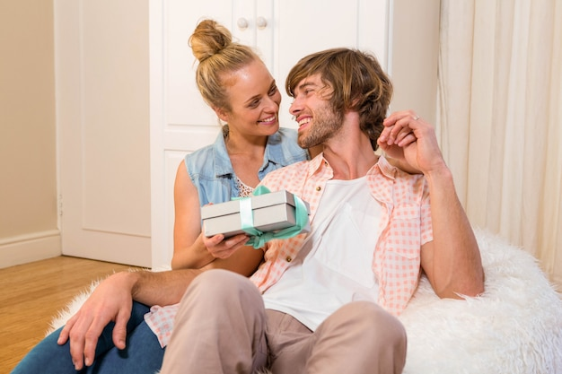 Красивая женщина, предлагая парню подарок в гостиной Premium Фотографии
