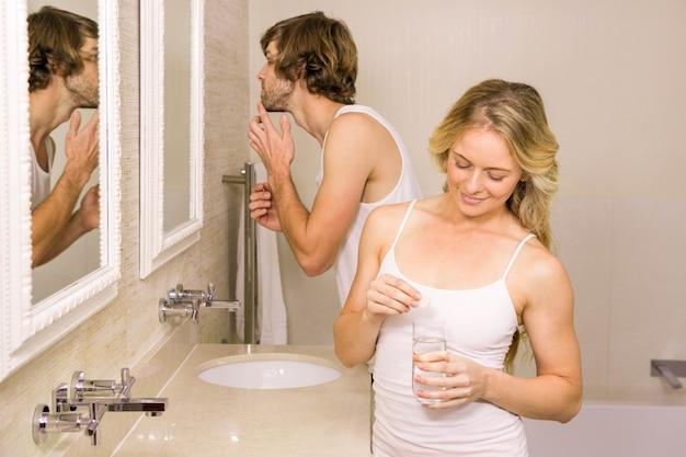 自宅の浴室で彼の歯を磨く彼女のボーイフレンドと一緒にピルを服用しているブロンドの女性 Premium写真
