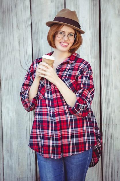 Улыбающаяся хипстерская женщина держит кофейную чашку Premium Фотографии