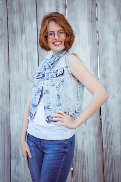 木製に対して彼女の腰に彼女の手で笑顔の流行に敏感な女性 Premium写真