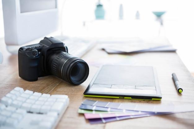 オフィスの机の上のデジタルカメラと色見本 Premium写真
