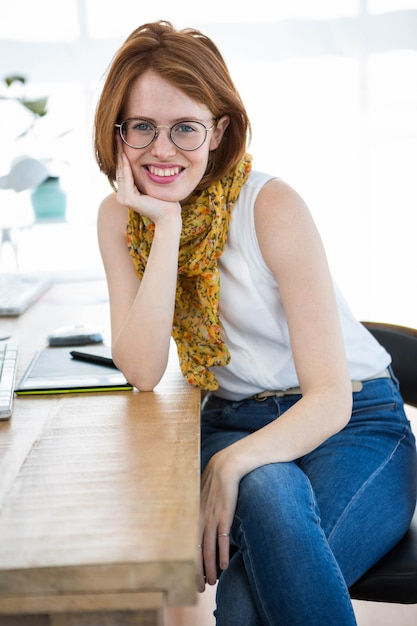 彼女の机に寄りかかって、彼女のオフィスに座っている美しい流行に敏感なビジネス女性 Premium写真