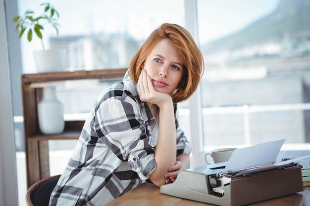 流行に敏感な女性彼女の机に座って、思考と彼女のタイプライターで入力 Premium写真