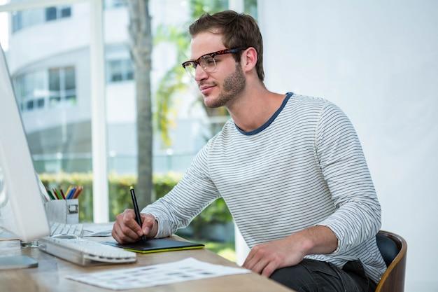 Красивый мужчина работает на компьютере и делать заметки в ярком офисе Premium Фотографии