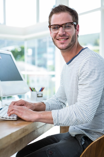 Красивый человек, работающий на компьютере в ярком офисе Premium Фотографии