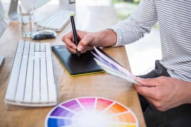 Мужские руки писать на цифровом планшете в ярком офисе Premium Фотографии