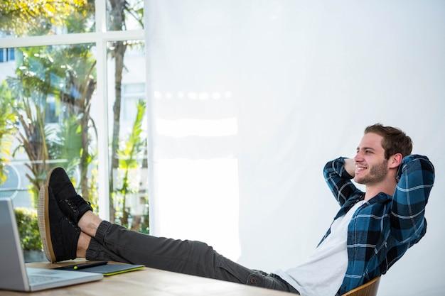 明るいオフィスで彼の机の椅子でリラックスしたハンサムな男 Premium写真