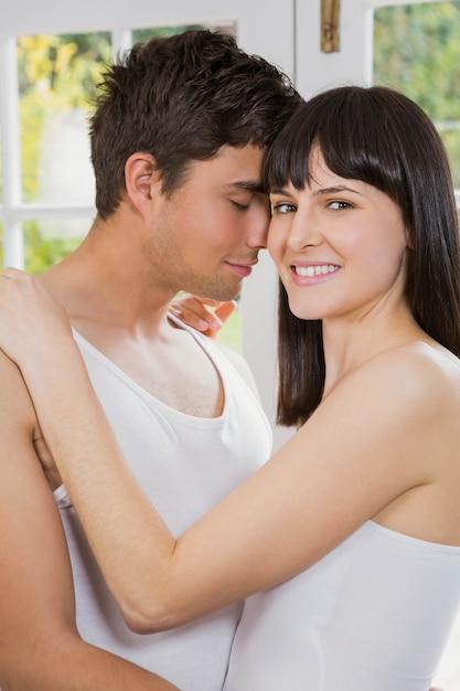 若いカップルの笑顔とリビングルームでお互いを抱きしめる Premium写真