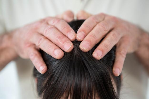 ヘルススパでマッサージ師からヘッドマッサージを受ける女性のクローズアップ Premium写真
