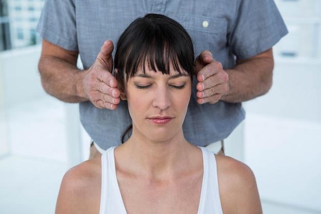 ヘルススパでマッサージ師からヘッドマッサージを受ける妊娠中の女性 Premium写真