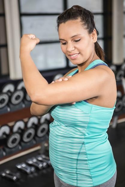 ジムで彼女の筋肉を示すスポーツウェアの女性 Premium写真