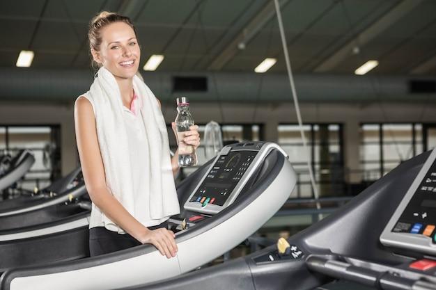 ジムで笑顔の女性飲料水 Premium写真