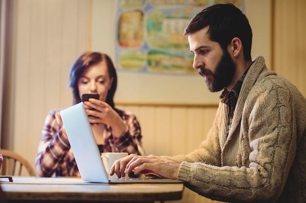 ノートパソコンと携帯電話を使用してカップル 無料写真