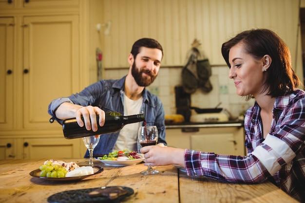 Мужчина наливает вино в бокал женщине Бесплатные Фотографии