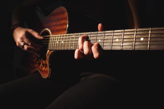 Женщина играет на гитаре в музыкальной школе Бесплатные Фотографии