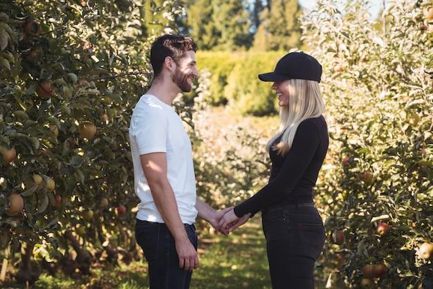 手を繋いでいるとリンゴ園に立っているカップル 無料写真