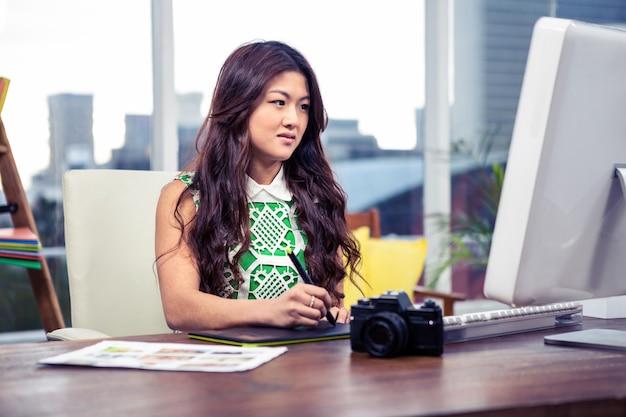 デジタルボードとオフィスでコンピューターを使用してアジアの女性に焦点を当ててください。 Premium写真