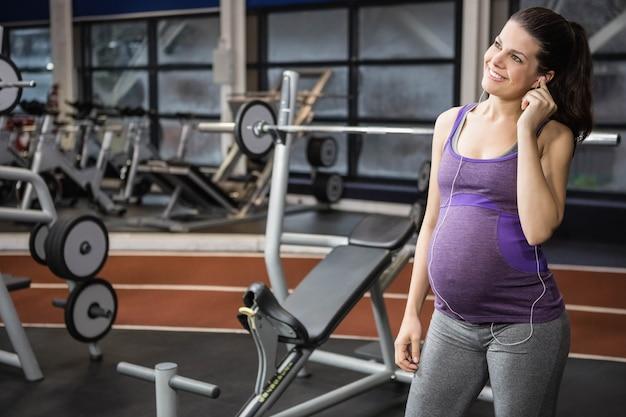 Беременная женщина слушает музыку в тренажерном зале Premium Фотографии