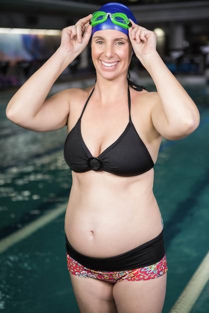 Улыбающаяся беременная женщина, стоящая рядом с бассейном в центре досуга Premium Фотографии
