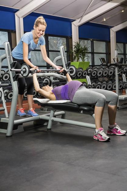 Усмехаясь тренер помогая штанге беременной женщины поднимаясь на спортзале Premium Фотографии