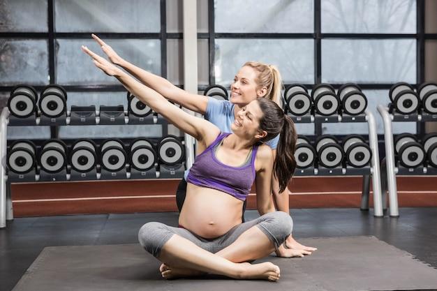 トレーナーとジムで腕を伸ばして妊娠中の女性の笑みを浮かべてください。 Premium写真