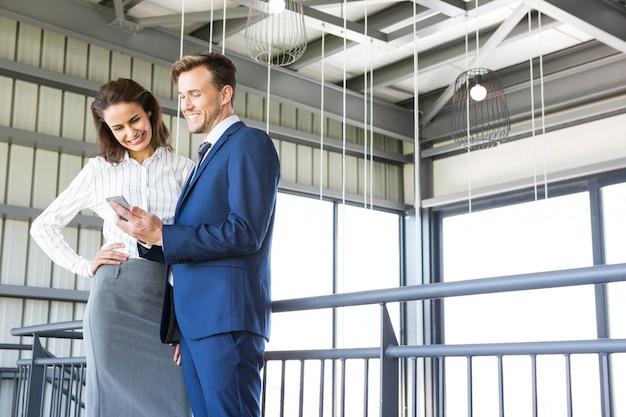 ビジネスマンやビジネスウーマンのオフィスでスマートフォンを見て Premium写真