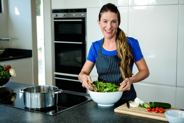 台所でサラダを投げ笑顔の女性 Premium写真
