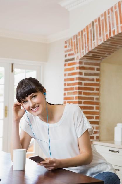 キッチンでコーヒーを飲みながらスマートフォンで音楽を聴く若い女性 Premium写真