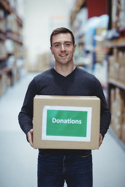 倉庫で募金箱を保持しているカメラに笑顔のボランティア Premium写真