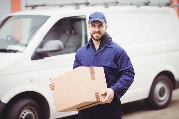 彼のバンの前にボックスを保持している配達人 Premium写真