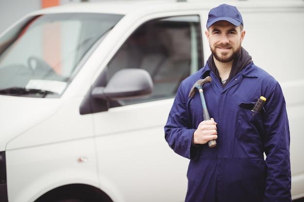 彼のバンの前でハンマーを持って修理 Premium写真